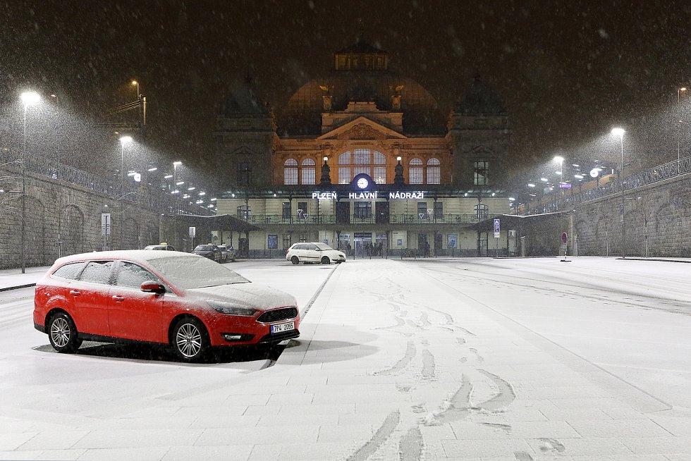 Noční sněžení v centru i okrajových částech Plzně. Na snímku hlavní nádraží ČD.