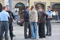 Policisté odvedli Davida Brabce (v kostkované mikině)  a Víta Jindru (s culíkem zády) na služebnu k vysvětlení jejich činu.