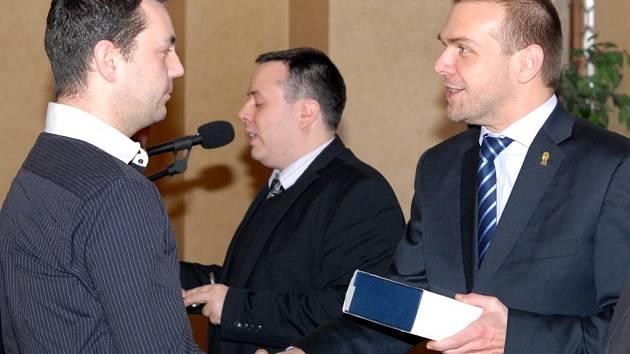 Pavel Hrach (vlevo) přebírá z rukou primátora plaketu. Oceněn byl za záchranu života tonoucího na Boleveckém rybníku