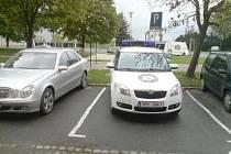 Auto městské policie zaparkované na místě pro invalidy