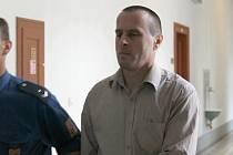 Vězeňská eskorta přivádí Maďara Istvána Orbána do jednací síně.