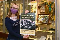 Marie Mušková kurátorka národopisného odd. Západočeského muzea v Plzni ukazuje plakát k výstavě Skauti v boji za svobodu.