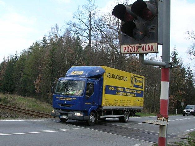 Železniční přejezd u Kaznějova, místo v němž se trať kříží se silnicí I/27, řidiče k rychlé jízdě přímo svádí