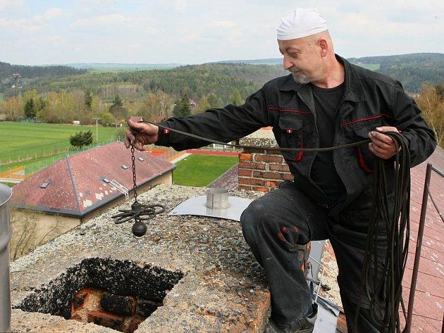 Kominík Pavel Krysl čistí komín na budově Základní školy v Dýšině