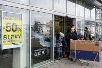 Zákazník vycházející z Electro Worldu v Plzni u obchodního centra Tesco na Rokycanské třídě.