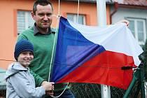 Plzeňan Aleš Brand se synem Ondřejem právě věší českou vlajku na stožár, který mají na zahradě.