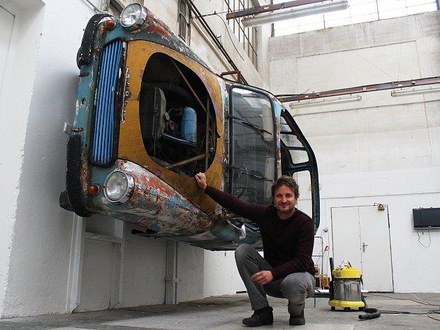 Škodu 1202 drží na stěně masivní háky, zavěsit ji musel vysokozdvižný vozík. Na snímku je i autor výstavy Benedikt Tolar.