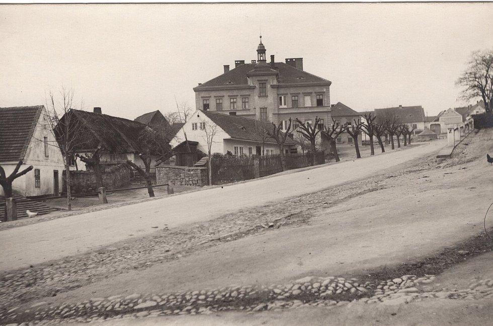 Na snímku je zachycena Bolevecká náves směrem ke staré škole ve 30. letech 20. století.