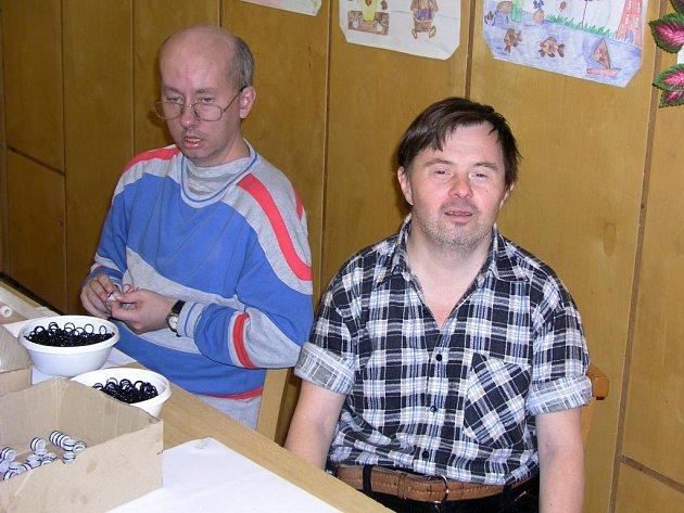 """Jiří Kestler (na snímku vpravo) pracuje v chráněné dílně plzeňského Stylu již 16 let. Nyní mu spolu s dalšími 24 kolegy hrozí vyhazov kvůli zmenšené podpoře státu. """"Líbí se mi tady, nechci jít pryč,"""" říká  smutně 40letý muž"""