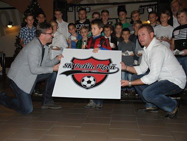 Za dohledu trenérů divizního áčka Radka Vodrážky (vlevo) a Jana Pletichy pokřtil  nové logo  klubu SK Petřín Plzeň  David Votípka (uprostřed), nejlepší střelec týmu žáků ročníku 2008.