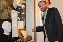 Kurátor výstavy Michal Chmelenský ukazuje na vitrínu s posmrtnými maskami
