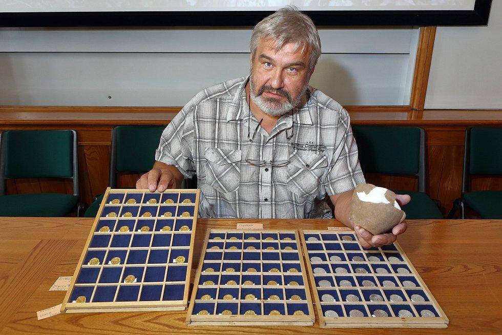 Archeolog Milan Metlička ze Západočeského muzea ukazuje mince z pokladu, který našli lidé na procházce v lese na Tachovsku. Poklad obsahuje zlaté a stříbrné mince ze 14. století, které byly uloženy v nevelké nádobě.