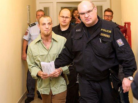 Policejní eskorta vede muže obviněného z pokusu o vraždu.