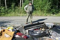 Hromad plných plastových autodílů, molitanu, gum  a podobně je podél cesty v lese u Sulkova několik. Na snímku  u jedné z nich  stojí nespokojený myslivec Milan Costenaro