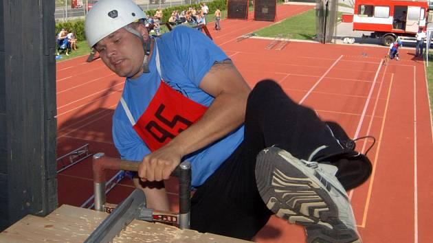 Jeden ze závodníků při výstupu na čtyřpatrovou cvičnou věž v průběhu první disciplíny  krajského kola soutěže v požárním sportu