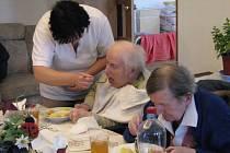 Pracovnice domova pro seniory v Plzni na Bílé Hoře krmí dva z klientů při obědě. Senioři jsou často nepohybliví a závislí na druhých