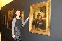 Ivana Jonáková při přípravě výstavy Na okraji davu s obrazem Jaroslava Čermáka, který působil v 19. století jako salonní umělec v Paříži, ale nevyhýbal se ani sociální tématům