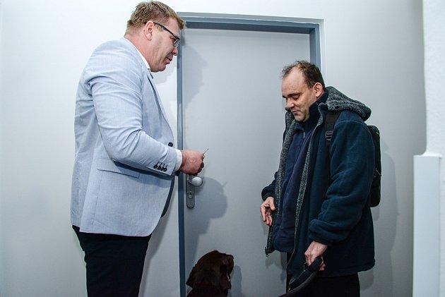 Radní David Šlouf (vlevo na snímku) předává klíče prvnímu nájemníkovi Petrovi Brožkovi.