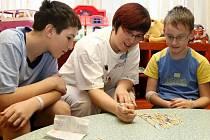 Devítiletý MIrek Šamberger (vpravo)  jí vypočítané jídlo už od svých tří let, kdy u něj lékaři cukrovku zjistili. Na snímku je společně s Karlem  Kouklem a herní terapeutkou z fakultní nemocnice.