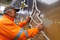 Miloslav Janout montér veřejného osvětlení PMDP instaluje výzdobu na vánoční tramvaj