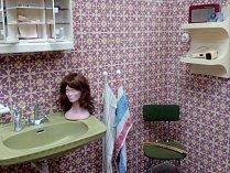 Retro koupelna jako vyšitá. Nesmí chybět plastová galerka se zrcadlem ani starožitný fén na poličce.