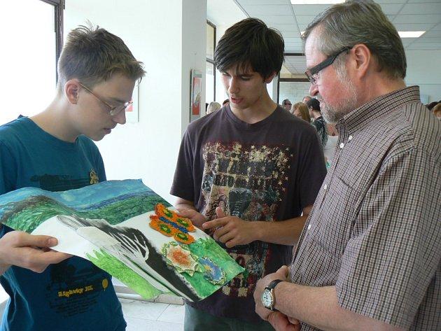 Žáci vysvětlují docentu Beranovi myšlenku obrazu, který mu s díky věnovali za možnost vystavovat v galerii