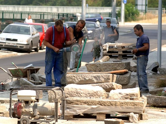 Za dělníky je vidět nová silnice od Pražské ulice k poliklinice, která je již zprovozněna