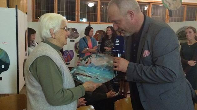 Seniorka přišla vydražit malířskou paletu pro svoji stoletou kamarádku, které se prý moc líbí. Na snímku s moderátorem benefiční aukce Janem Kovaříkem.