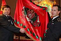 Velitel HS Skvrňany Vlastimil Malina (vlevo) ukazuje spolu se starostou sboru Markem Grollmussem (vpravo) novou zástavu hasičského sboru. Ta byla vyrobena právě u příležitosti 130. výročí založení sboru