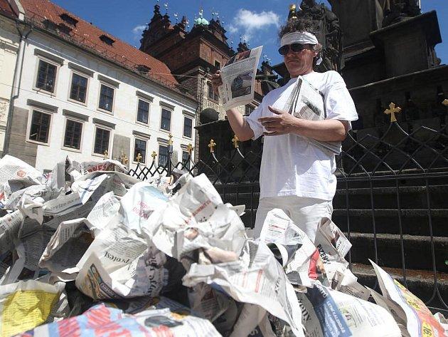 Americký umělec Peter Grzybowski u morového sloupu v rámci svého představení pohazoval na hromadu stránky novin