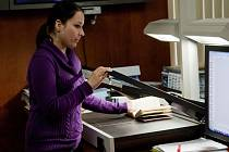 Pracovnice zámku Kozel skenuje jeden ze 26 tisíc svazků knih. Zámek se do digitalizace knihovny pustil před třemi roky