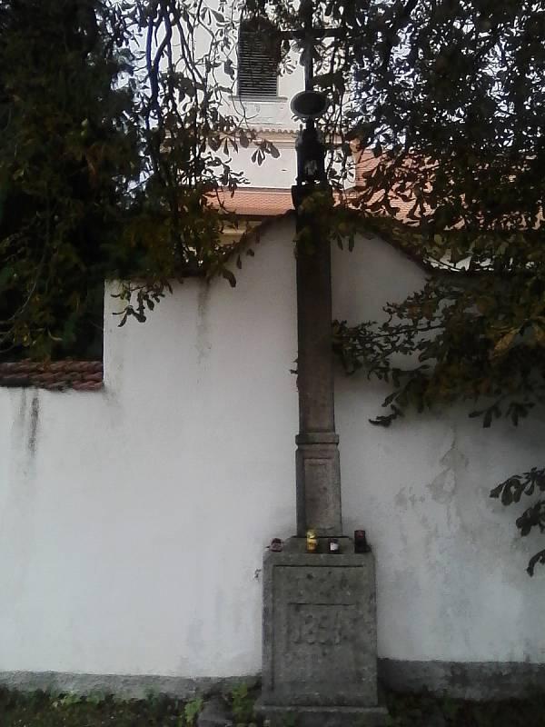 Kříž u kostelní zdi v Petrovicích z roku 1853.