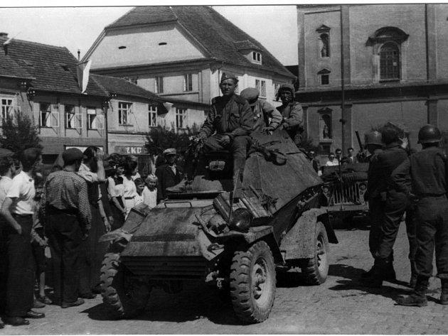 Březnické náměstí dne 10. 5. 1945 zažilo jako jedno z prvních míst příbramského regionu setkání amerických vojáků (vpravo) se sovětskými, kteří sem přijeli s obrněným vozem BA-64.