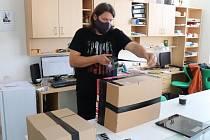 Učitel Tomáš Bílek při balení vybraných ochranných pomůcek v milínské škole.
