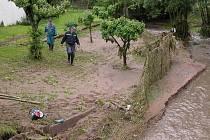 Břeh rozvodněného potoka v Kamýku. Majitelé pozemku vlevo požádali už ráno hasiče o pomoc, když jim voda strhla plot.