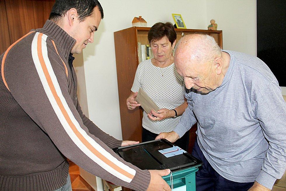 První den krajských voleb. Jaroslav Herzán špatně chodí, proto požádal jinecké komisaře o donášku urny domů.