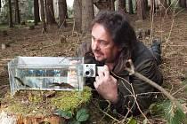 Karel Kerouš z České inspekce životního prostředí fotografuje čolky velké u rybníčku.
