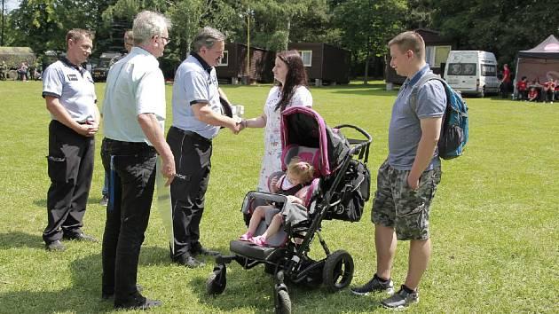 Zástupci policie předávají šek na vybranou částku rodičům malé Laurinky.