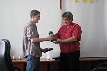 Student Petr Přibyl přebírá od starosty Josefa Řiháka dary jako poděkování za projevenou duchapřítomnost