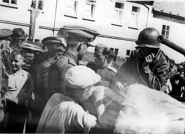 Ze setkání sovětských a amerických vojáků vBřeznici na náměstí 10.5.1945. Vpravo sradiostanicí first sergeant (nadrotmistr) 4.tankové divize 3.americké armády předává svým nadřízeným hlášení onavázání kontaktu spříslušníky sovětské armády (vlevo).
