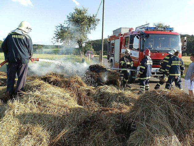 Požár balíků slámy na přívěsu.