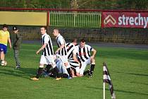 Fotbalisté Dobříše se radují z gólu, který znamenal jejich první tříbodové vítězství v sezoně. Dal ho Robert Talůžek (klečící vlevo).