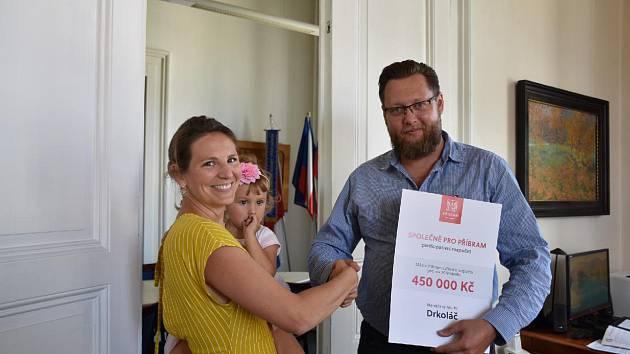Předkladatelka vítězného návrhu Michaela Alimov přebírá od starosty města Jana Konvalinky symbolický šek na projekt Drkoláč.