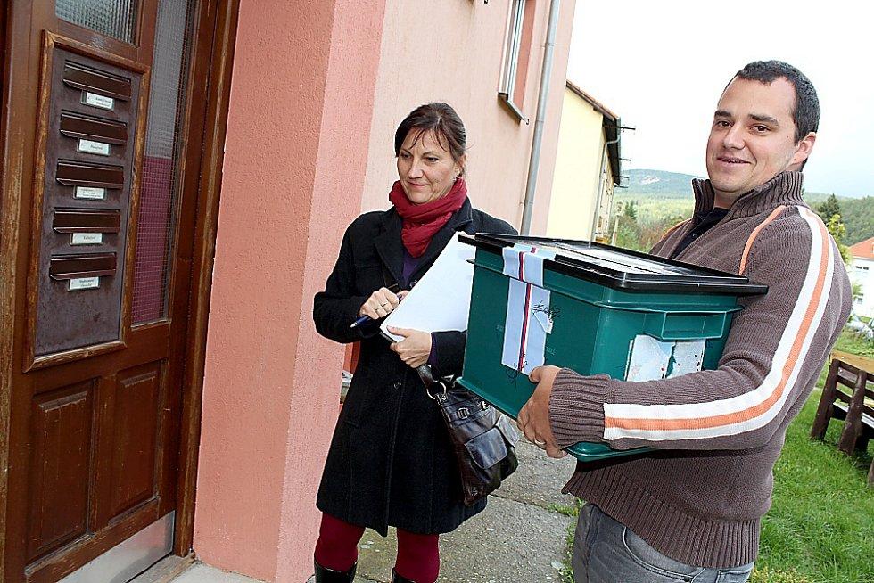 První den krajských voleb. Komisaři v Jincích nesou schránku k nemocnému voliči domů.
