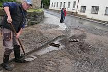 Zaměstnanec Kamýku Karel Řiháček při úklidu nánosů štěrku z křižovatky. Pod hromadami náplavy nebylo možné najít ani kanály.