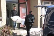 Pracovníci pohřební služby vynášejí z domu tělo.