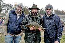RYBU Z MUSÍKA budou Ondřej Slanina (vlevo) a Filip Saljer připravovat v televizním pořadu Kluci v akci. Nebude to ale kapr, kterého na společném snímku s nimi drží v ruce rybář Oldřich Pecha, ale štika. Tu si odtud také odváželi.