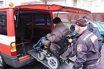 Hasiči nakládají figuranta na vozíku.