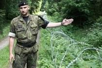 Mluvčí vojenské policie Jan Čermák ukazuje novinářům žiletkový plot na kótě