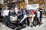 Elektrické minirypadlo s týmem produktových manažerů a inženýrů.